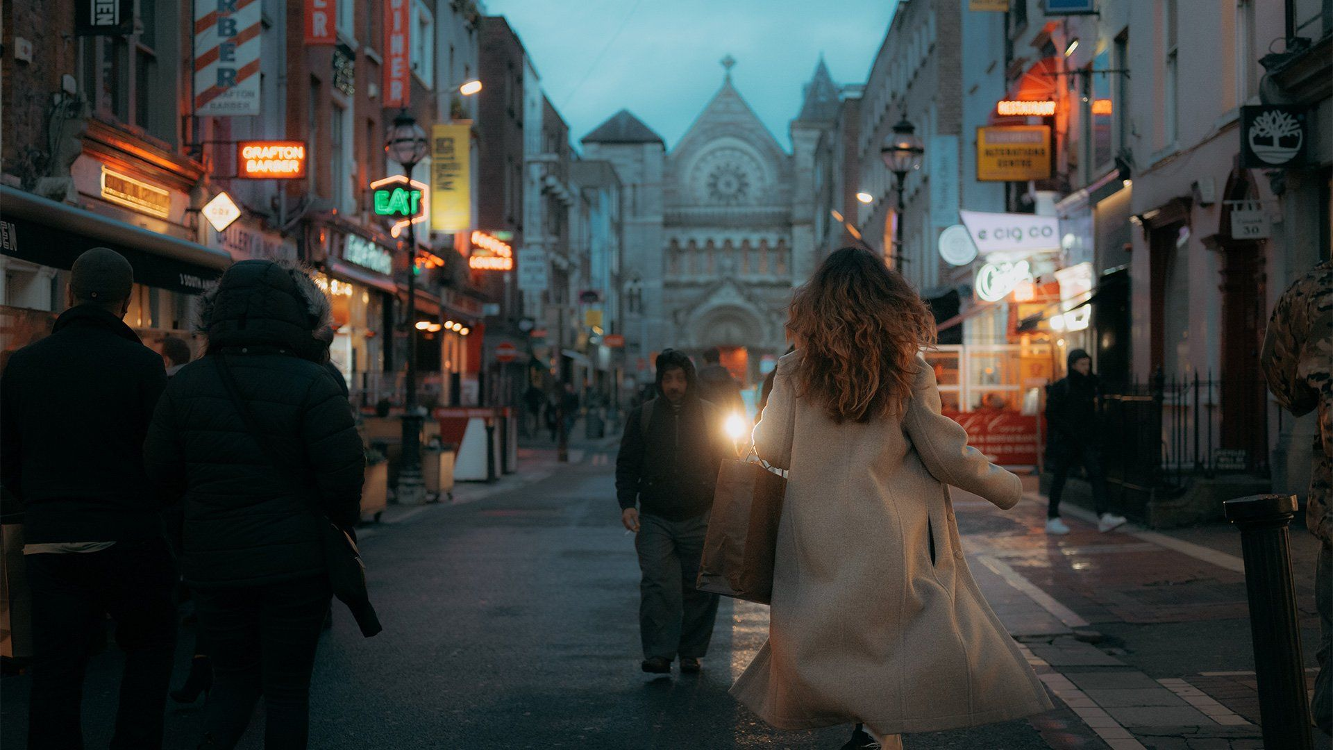 A woman running down a bustling street at dusk.